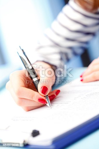 Close-up portrait of young businesswoman sitting at desk and signs the contract.
