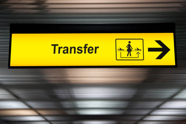 sign transfer with arrow for direction for transit passenger to change air plane for destination. yellow transfer for connecting flight sign at the airport stock photo