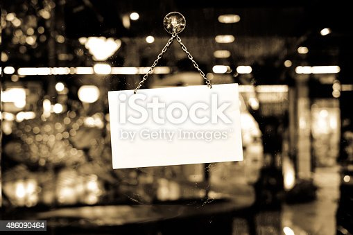 istock Sign with space for text hanging in a shop window 486090464