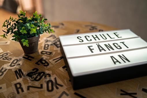 "Sign with the slogan ""School begins"" in German language that means ""School begins"""