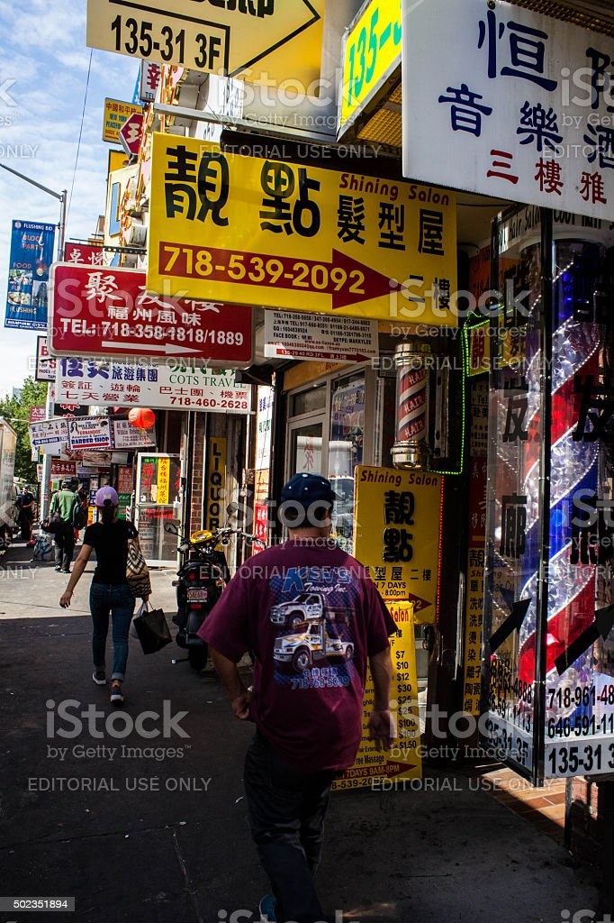 Signage overload along sidewalk in Flushing Queens' Chinatown stock photo