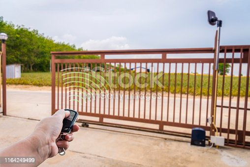 Signal of remote control when person open automatic gate at house for home security system with sunlight rays