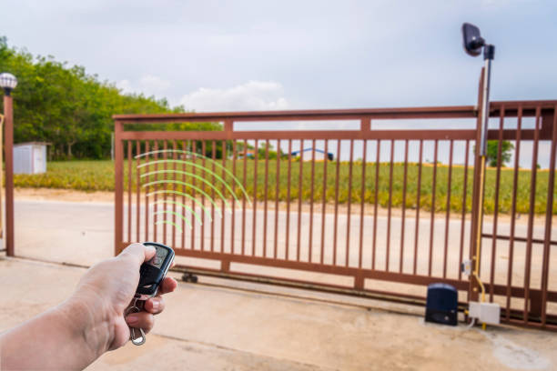 Signal of remote control when person open automatic gate at house for home security system with sunlight rays Signal of remote control when person open automatic gate at house for home security system with sunlight rays automatic stock pictures, royalty-free photos & images
