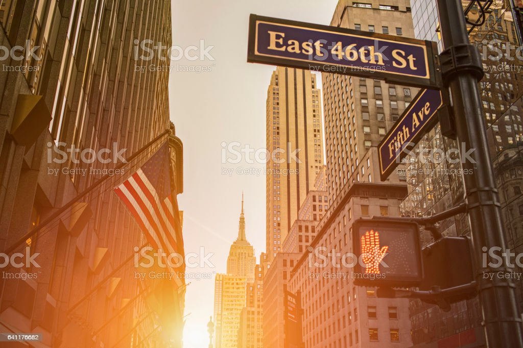 Signboard and Empire State Building during sunset stock photo