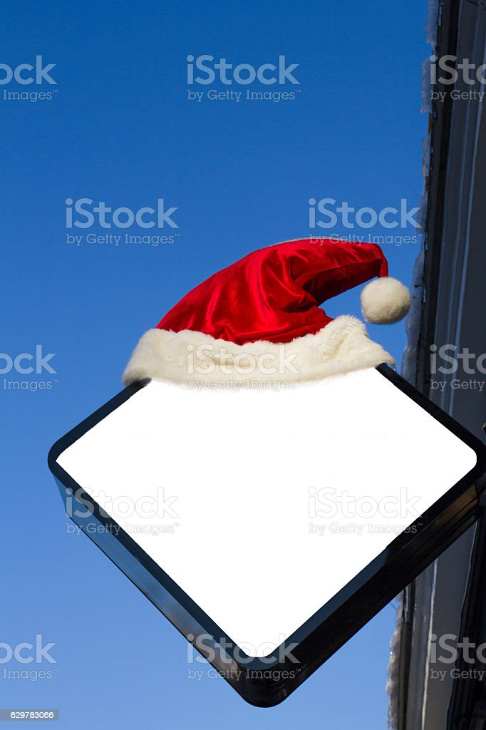Signboard on wall. Mock up with Christmas decoration, Santa hat stock photo
