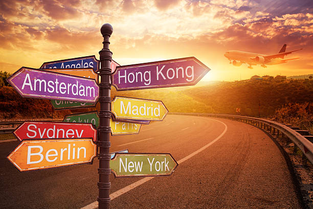 signboard with directions to countries - travel destinations stock photos and pictures