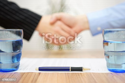 istock signed contract with handshake in blur, focus on pen 476820012