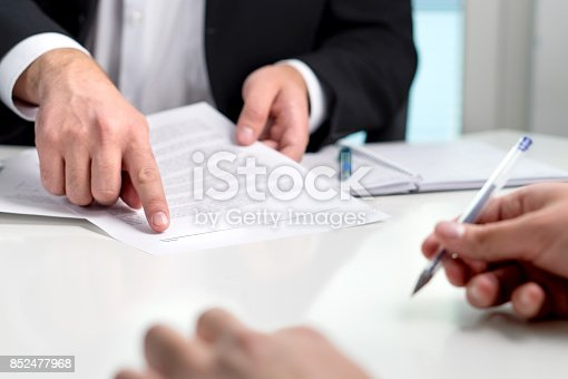 istock Signing a contract or agreement. Banker or lawyer showing client the line for autograph in a document paper. Business man with a customer in office making deal. Employee hired. 852477968