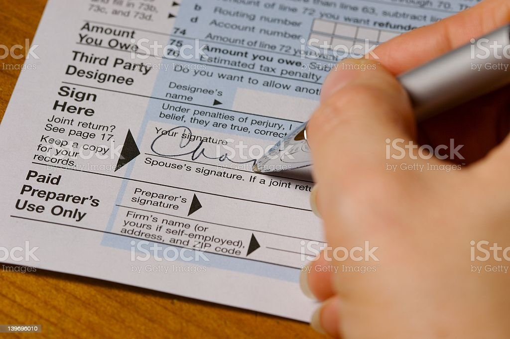 Signing Blue Tax Form stock photo