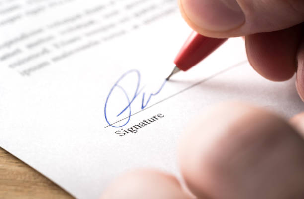 Signing contract, lease or settlement for acquisition, apartment lease, insurance, bank loan, mortgage or business buyout. Man writing name and autograph with pen. The signature is made up. stock photo