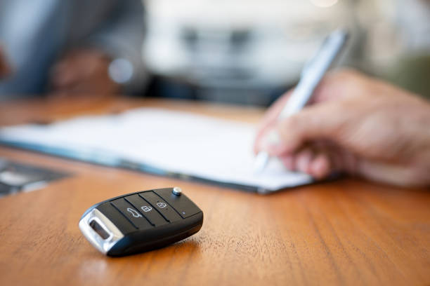 Signing contract of new car Car keys on desk with man signing purchase documents in background. Closeup of black modern car keys while hand complete the insurance policy or rental documents. Guy buying new car at dealership. car key stock pictures, royalty-free photos & images