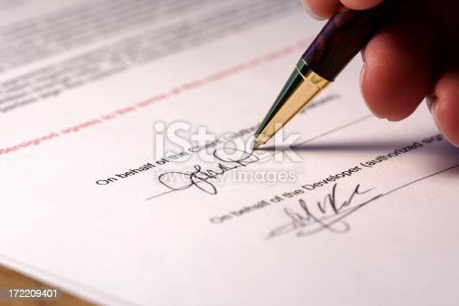 Macro shot of someone signing a contract.  Focus is on the signature and the end of the pen.