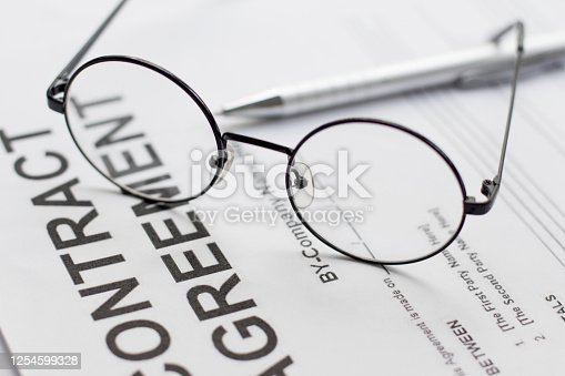 istock Signing contract with glasses nearby 1254599328