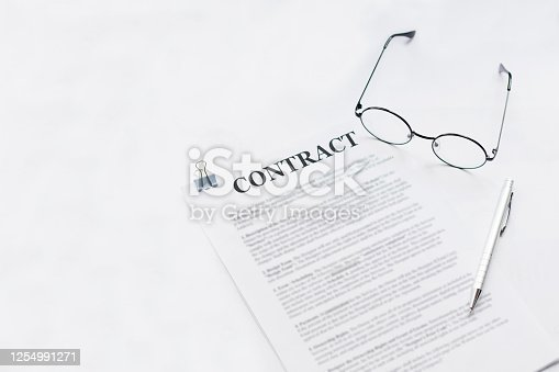 istock Signing contract with glasses nearby 1254991271