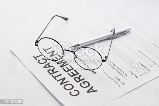 istock Signing contract with glasses nearby 1254991283