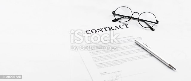 istock Signing contract with glasses nearby 1255291786