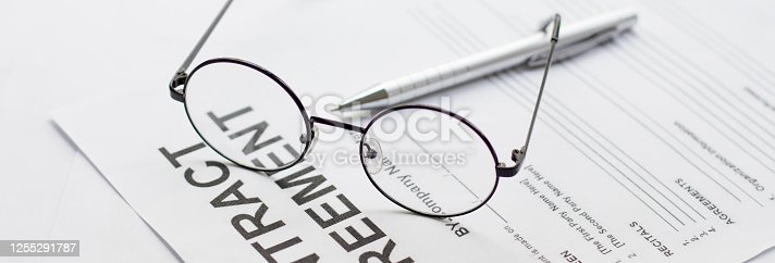istock Signing contract with glasses nearby 1255291787