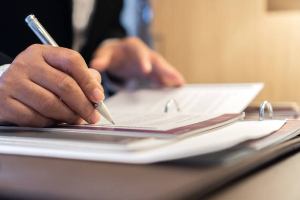 Signing Document report and business busy concept: Businessman manager hands holding blue pen for reading and sign in paperwork or documentation files on computer modern corporate office background. stock photo