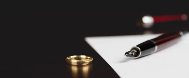 Das Signieren oder Schreiben von Scheidungsdokumenten-Konzept auf dem Tisch mit dunklem Hintergrund – Foto
