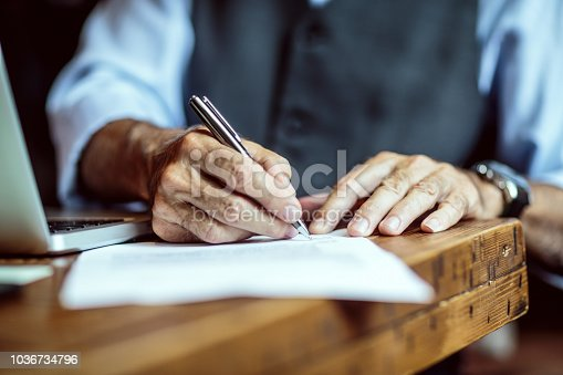 Close up view of senior male hands while signing the document.
