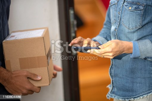 Unrecognisable woman signing receipt on a smartphone for receiving her package while unrecognisable delivery man is holding it.