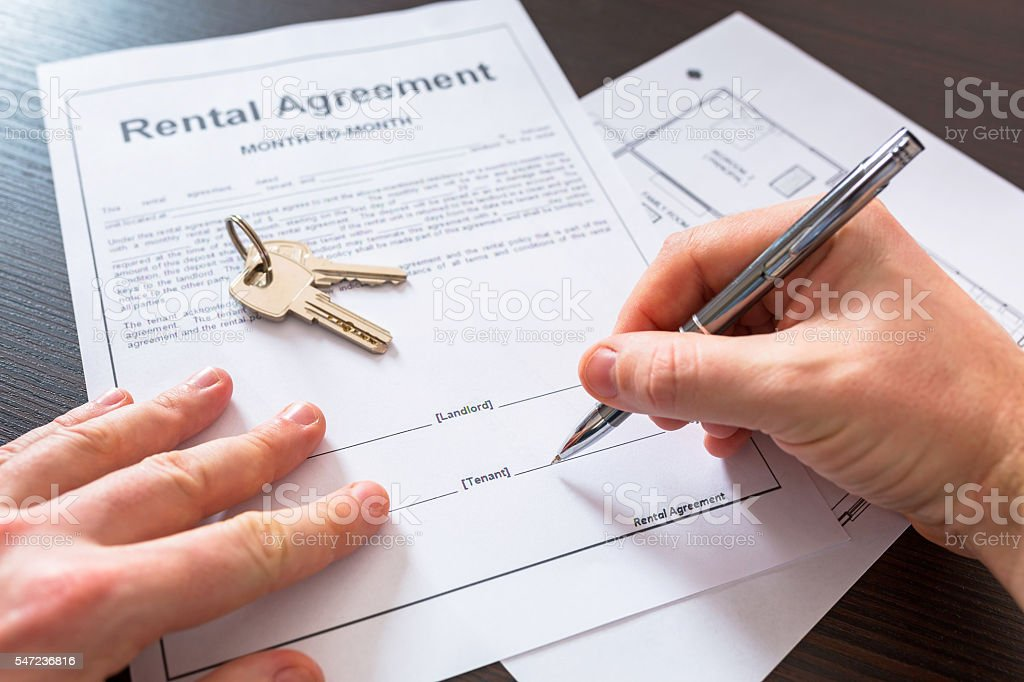 Signing rental agreement contract stock photo