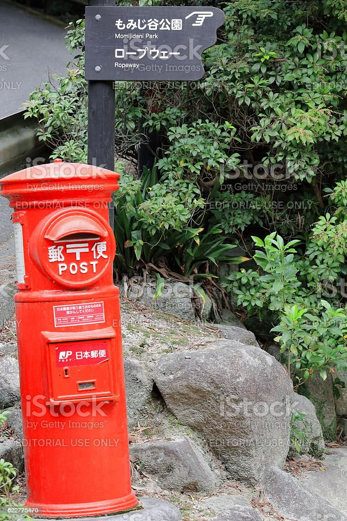 Signpost and red Japan Post mailbox. Miyajima-Japan. 6965 stock photo