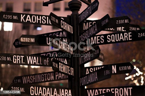 istock Signpost. Directional marker to world landmarks at night in dowtown. 1085443496