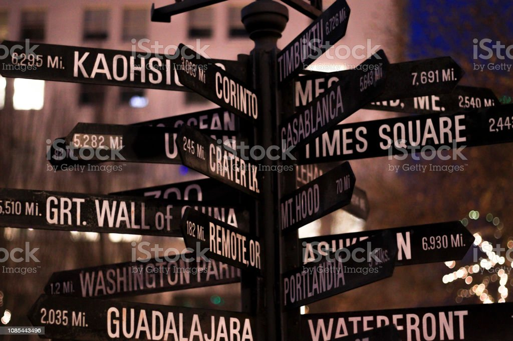 Signpost. Directional marker to world landmarks at night in dowtown. stock photo
