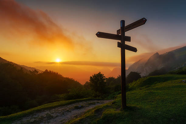 signpost in the mountain at sunset - directional sign stock photos and pictures