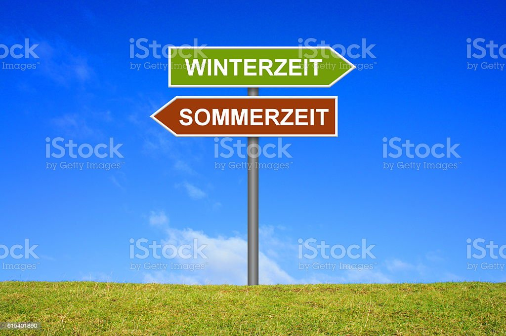 Signpost winter time summer time german stock photo