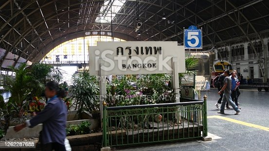 Bangkok, Thailand - 11 July, 2019: Signpost with name of city. Hua Lamphong main railroad station of state railway transport, SRT. Passengers on platform near sign board. People and trains on tracks