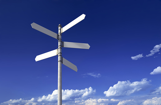 Signpost with three blank signs on sky backgrounds