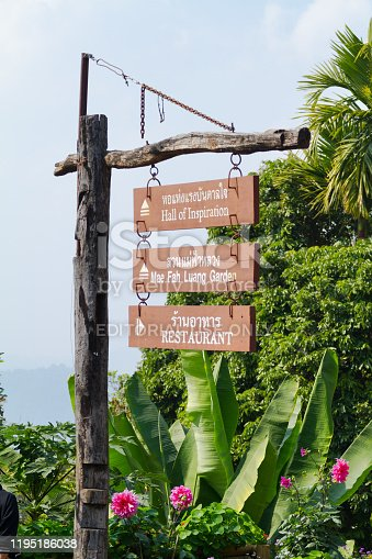 Signs and fingerposts on Doi Tung mountain in arrival area. In background are tropical trees and plants. Doi Tung mountain in thai highlands of  Mae Fa Luang District in provinz Chiang Rai and offers gardens, nature, coffee plantation and  more.