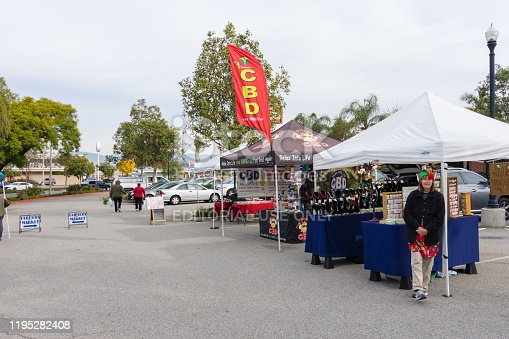Corona, CA USA - December 21, 2019: Saturday Farmer's Market in center of city with local growers, vendors, artisans, and bakers selling products. CBD or Cannabidiol sales and local jewelry artist