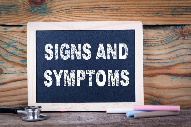 signs and symptoms. Chalkboard on a wooden background stock photo