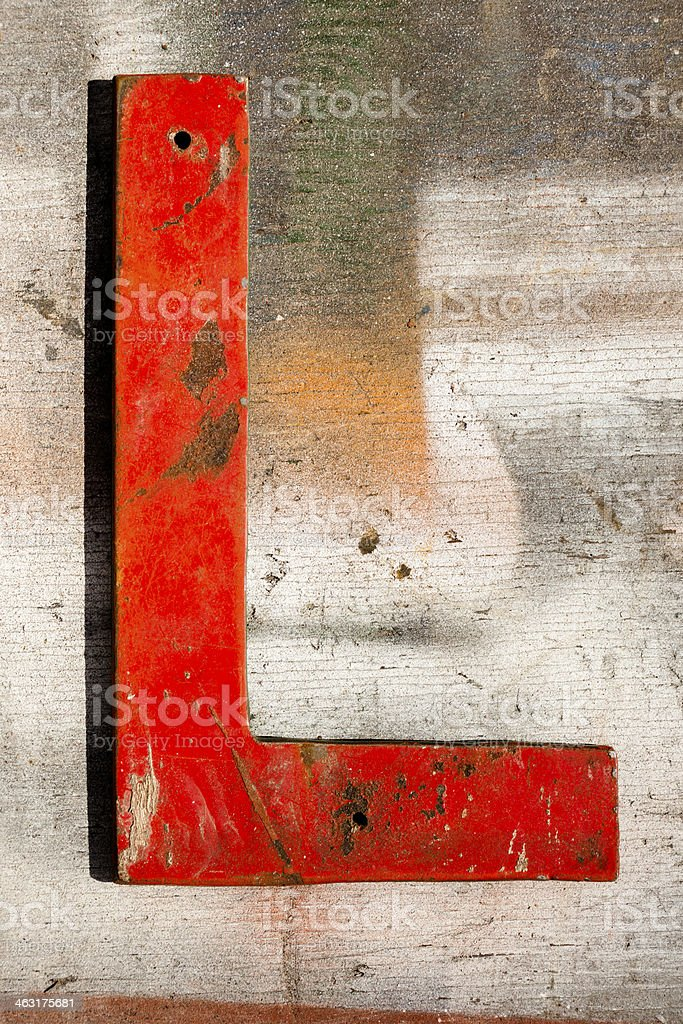 Signs: Capital letter 'L' on wooden, grunge plank. stock photo