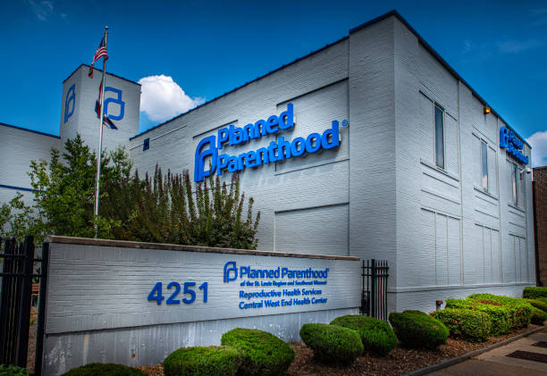 Signs for Planned Parenthood a women's health provider displayed on the side of a facility in Central Westend Saint Louis, MO--Aug 3, 2019 American flag flies next to the last abortion clinic in the state of Missouri with blue and cloudy sky in background. planned parenthood federation of america stock pictures, royalty-free photos & images