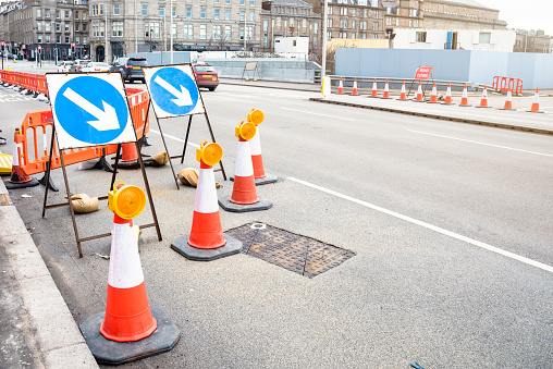 Signs, traffic cones and barriers indicating the closure of a street lane because of roadworks