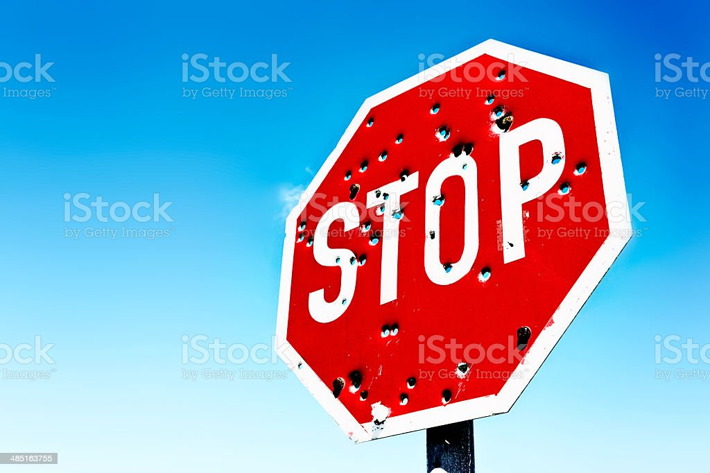 Signs of the times! Bullet-riddled traffic Stop sign stock photo