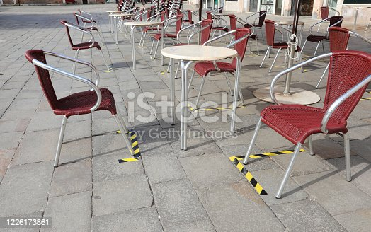 Signs on the ground to space the tables and chairs of an outdoor cafe without tourists in Venice in Italy due to the Corona Virus epidemic