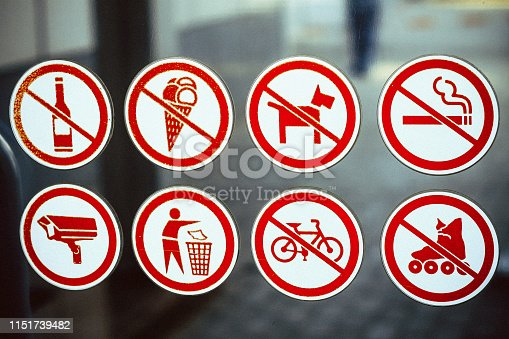 signs of prohibition of drinking alcohol, eating ice cream, dog walking, smoking, rollerblading and cycling on a glass surface; a sign to throw garbage in bins; video surveillance sign; yellow frames