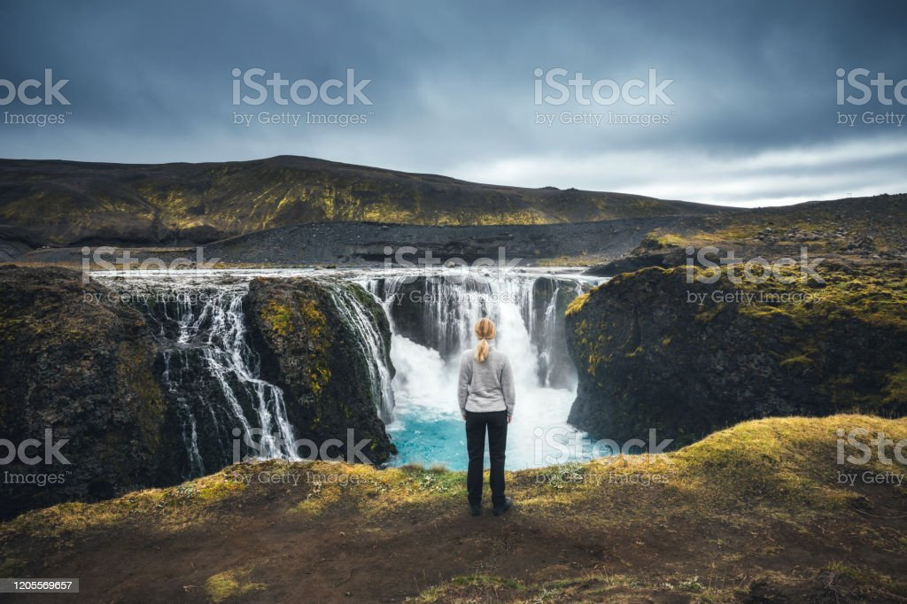 Sigoldufoss In Iceland Woman standing in front of beautiful Sigoldufoss waterfalls in Iceland's highlands. Above Stock Photo