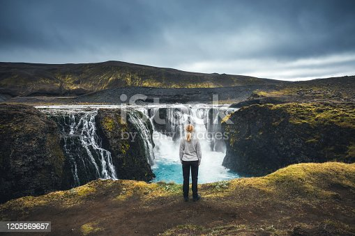 Woman standing in front of beautiful Sigoldufoss waterfalls in Iceland's highlands.