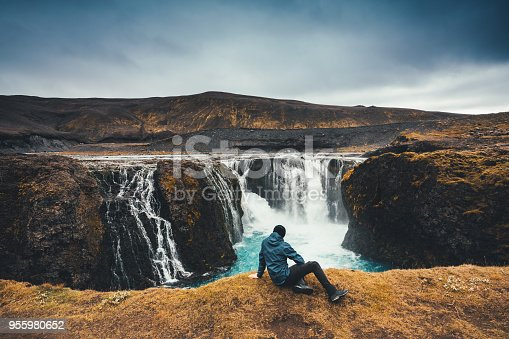 Man sitting on top of beautiful Sigoldufoss waterfalls in Iceland's highlands.
