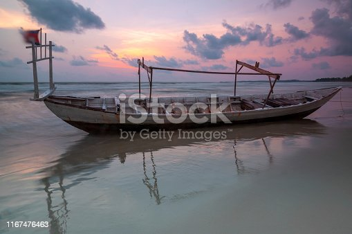 Long exposure of a fishing boat on Otres beach at sunset with blurred motion (waves and cambodian flag), Sihanoukville, Cambodia.