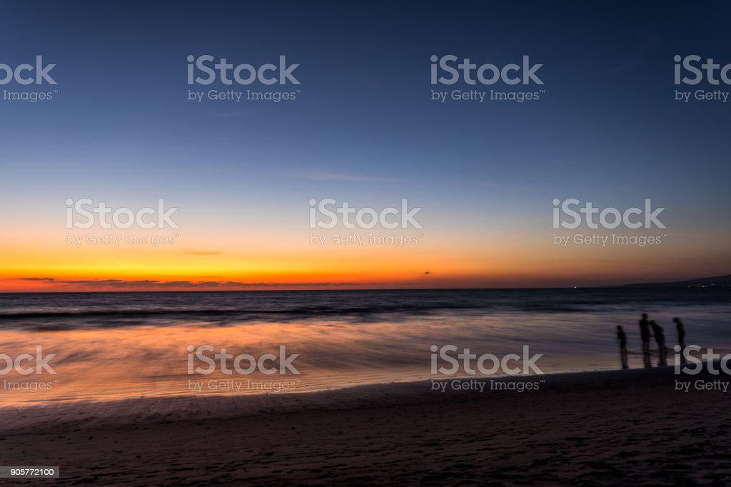 sihouette of people paying on the beach at sunset stock photo