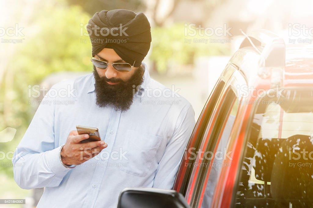 Sikh man using smartphone stock photo