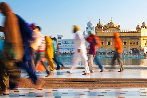 Sikh pilgrims walking past Golden Temple in India stock photo