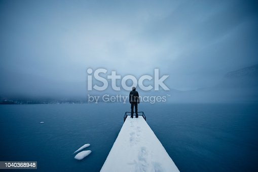 Peaceful winter morning by the frozen lake. Man is standing on the pier.